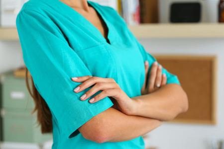 mani incrociate: Femmina medicina terapeuta medico le mani incrociate sul petto in ufficio primo piano. Assistenza medica, aiuto o concetto di assicurazione. Medico in uniforme verde in attesa per il paziente di esaminare
