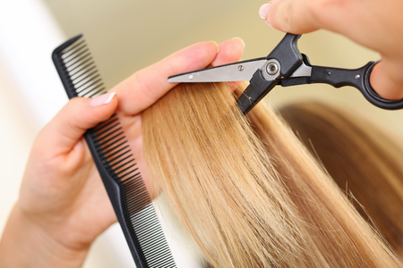 Female hand holding comb and hot thermal scissors cutting tips of long straight blonde hair lock closeup. Hairdresser salon, barber shop, perfect look, modern technique, new hairdo concept
