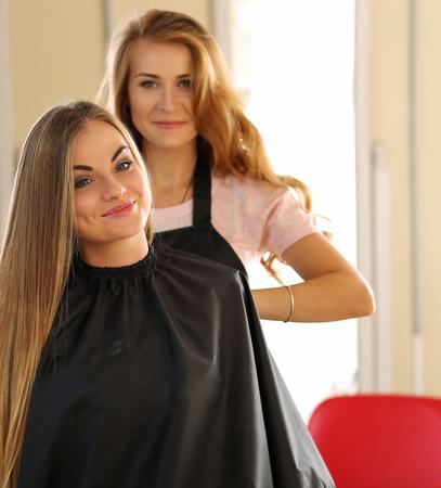 barbero: Hermosa peluquería femenina rubia mirando en el espejo y elegir el peinado adecuado para la sonrisa largo cabello del cliente. salón de peluquería, barbería, aspecto perfecto, peinado nuevo concepto Foto de archivo