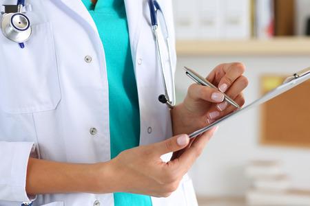Geneeskunde vrouwelijke arts hand met zilveren pen schrijft iets op klembord close-up. Medische zorg, verzekeringen, het voorschrijven, papier werk of carrière concept. Arts klaar om de patiënt te onderzoeken en te helpen