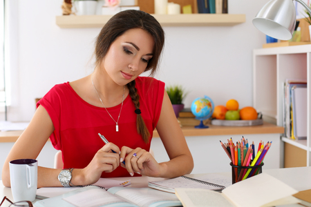 Female student at workplace portrait holding pen and looking in textbooks studying. Woman writing letter, list, plan, making notes, doing homework. Education, self development and perfection concept