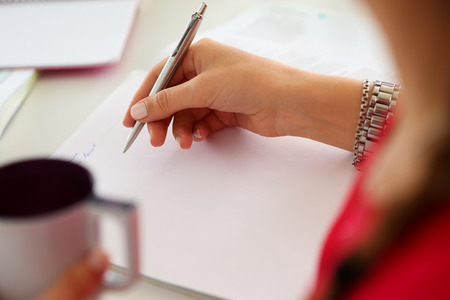 plan: Female hands holding cup of coffee or tea and silver pen closeup. Woman writing letter, list, plan, making notes, doing homework. Student studying. Education, self development and perfection concept