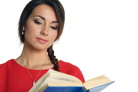 self development: Beautiful woman in red dress wearing plait reading blue book. Female young student holding textbook portrait isolated on white background. Education self development and perfection concept