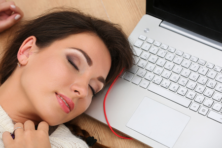 test deadline: Beautiful woman lying on laptop computer on wooden floor sleeping. Female student taking nap while studying or working. Education, communication, leisure, pastime, preparing for exams concept