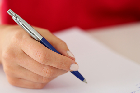 Female hand holding silver pen closeup. Woman writing letter, list, plan, making notes, doing homework. Student studying. Education, self development and perfection concept Stock Photo - 48582193