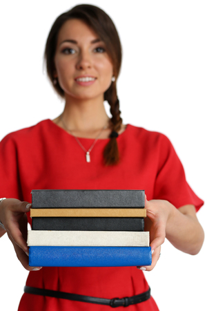 erudition: Woman wearing red dress holding in hands and giving or taking pile of books isolated on white background. Female student with textbooks. Education, studying, learning, teaching, bookshop concept