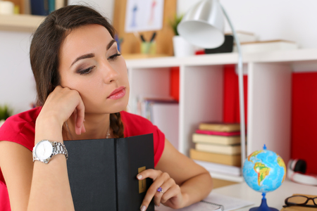 test deadline: Sad young female student in red dress holding black book and looking down portrait. Tired woman in despair at workplace suffering because of exam deadline concept. Education and self development Stock Photo
