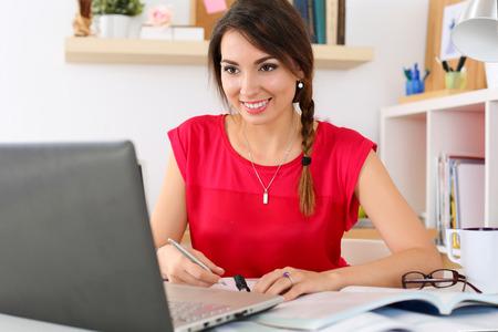 Vackra leende kvinnlig student använder online utbildningstjänst. Ung kvinna i biblioteket eller hemma rum ser i laptop skärm tittar utbildning. Modern studieteknologi koncept
