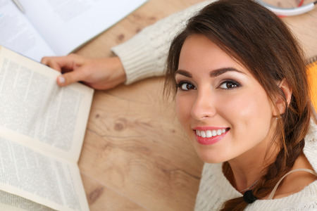 self development: Beautiful smiling woman portrait lying on floor reading book. Female student studying using textbooks. Education, learning, self development, leisure, pastime, library or bookshop concept