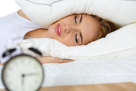 unpleasant: Young beautiful blonde woman lying in bed suffering from alarm clock sound covering head and ears with pillow making unpleasant face. Early wake up, not getting enough sleep, going work concept Stock Photo