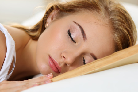 oversleep: Young beautiful blonde woman portrait lying in bed sleeping on book she read after hard working day tired. Sweet dreams, education, reading for examination, favourite literature, busy day concept Stock Photo