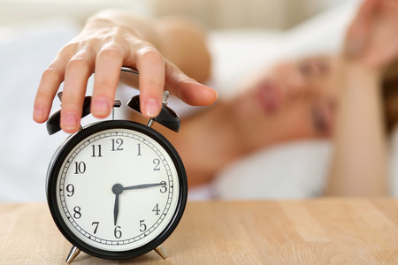 willing: Stretching hand of sleepy young woman trying kill alarm clock ringing awakening early morning. Early wake up, not getting enough sleep, getting work concept. Female arm willing turn alarm sound off