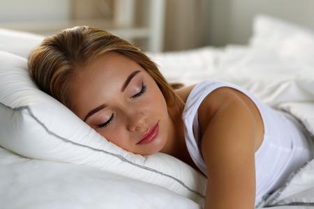 Mladá krásná osamělá plavovlasá žena portrét ležící v posteli spí doma pozdě ráno po náročném pracovním dni unavený. Sladké sny, dobrý den, nový den, víkend, volno, prázdniny koncept