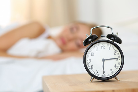Alarm clock standing on bedside table going to ring early morning to wake up woman in bed sleeping in background. Early awakening, not getting enough sleep, oversleep, getting work time concept