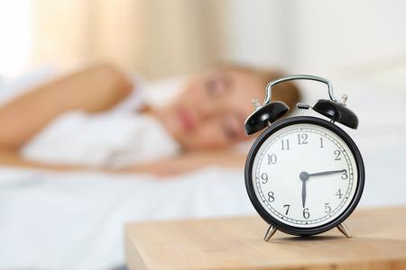 Sveglia in piedi sul comodino di andare a suonare la mattina presto per svegliarsi donna a letto a dormire in background. Il risveglio precoce, non dormire a sufficienza, dormire troppo, concetto di tempo di lavoro ottenendo