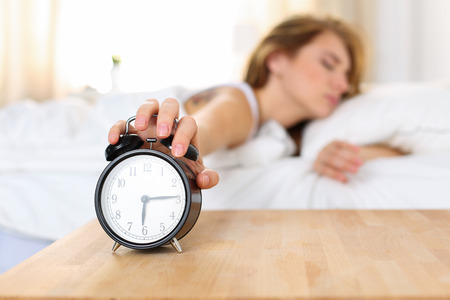 oversleep: Sleepy young woman trying kill alarm clock while bury face in pillow. Early wake up, not getting enough sleep, getting work concept. Female stretching hand to ringing alarm willing turn it off