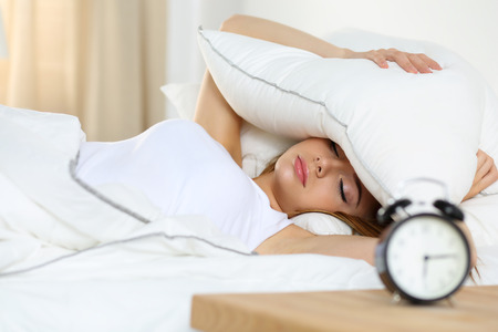 oversleep: Young beautiful blonde woman lying in bed suffering from alarm clock sound covering head and ears with pillow making unpleasant face. Early wake up, not getting enough sleep, going work concept Stock Photo