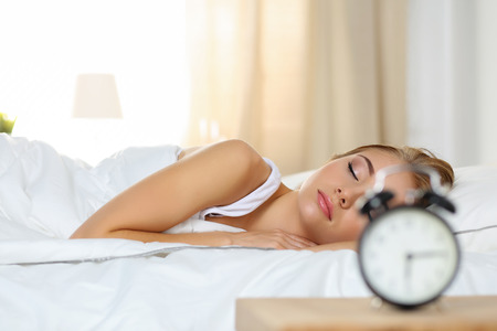 oversleep: Beautiful blonde woman peacefully lying in bed sleeping early morning while alarm clock going to ring awakening. Early wake up, not getting enough sleep, oversleep, getting work time concept