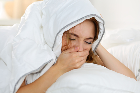 Sick young woman lying in bed suffering with cold covering nose with hand while sneezing. Female feeling sickness and unwell hiding head under blanket. Pregnancy, period premenstrual syndrome concept