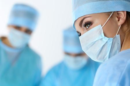 medicamento: Tres cirujanos en el trabajo que opera en quirófano salvar paciente y que mira el monitor vida. Equipo de medicina de reanimación con máscaras protectoras ahorro paciente. Cirugía y el concepto de emergencia