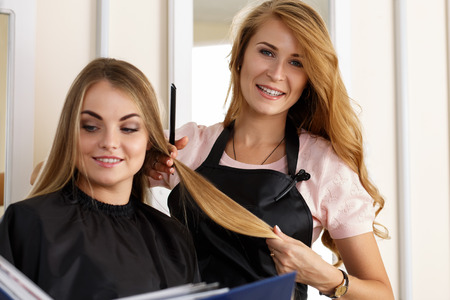 barber: Beautiful blonde female hairdresser holding lock of hair in hands and picking proper hairdo to smiling long haired customer. Hairdresser salon, barber shop, perfect look, new hairdo concept