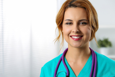 therapeutist: Beautiful charming friendly smiling female medicine therapeutist doctor standing in office and looking in camera. Medical help, physician reception or insurance concept