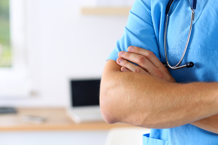 therapeutist: Male medicine therapeutist doctor hands crossed on his chest in office closeup. Medical care, help or insurance concept. Physician wearing blue uniform waiting for patient to examine