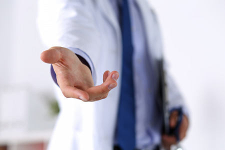 Male medicine doctor offering helping hand in office closeup. Friendly and cheerful gesture. Medical cure and tests advertisement concept. Physician ready to examine and save patient Foto de archivo