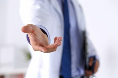 medicamento: Masculino medicina médico oferta mano amiga en el cargo de primer plano. Gesto amable y alegre. Cura médica y pruebas anuncio concepto. Médico dispuesta a examinar y guardar paciente Foto de archivo