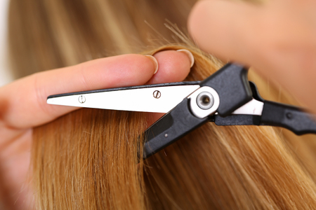 lock concept: Female hand holding hot thermal scissors cutting lock of long straight blonde hair closeup. Hairdresser salon, barber shop, perfect look, modern technique, new hairdo concept Stock Photo