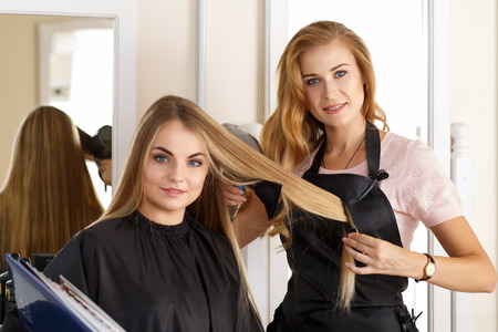 hairdressing: Beautiful blonde female hairdresser holding scissors, comb and hairdryer in hands and picking proper hairdo to smiling long haired customer. Hairdresser salon, barber shop, perfect look concept