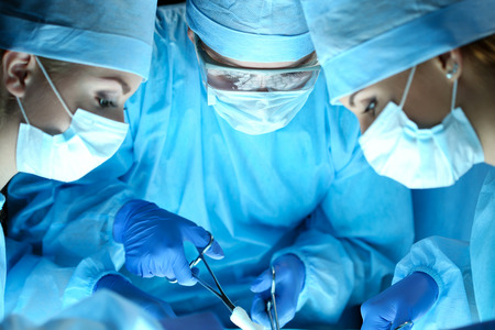Three surgeons at work operating in surgical theatre. Resuscitation medicine team wearing protective masks saving patient. Surgery and emergency concept Foto de archivo