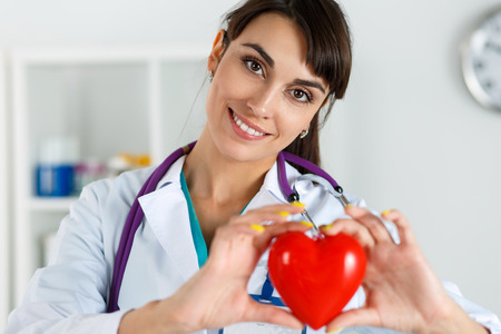 prophylaxis: Beautiful smiling female doctor holding red heart in front of chest closeup. Medical help, prophylaxis, insurance, surgery and resuscitation concept. Cardiology care,health, protection and prevention
