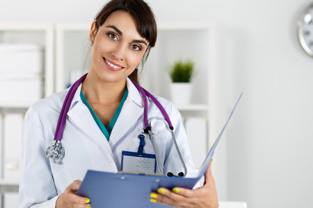 standing reception: Beautiful charming friendly smiling female medicine therapeutist doctor standing in office, holding document pad and looking in camera. Medical help, physician reception or insurance concept
