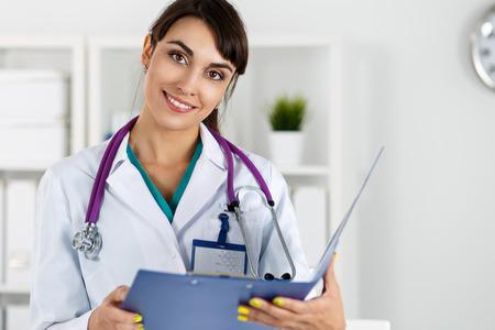 recepcion: Romántico medicina femenina sonriente hermosa terapeuta médico permanente en la Oficina, sosteniendo el documento almohadilla y mirando a puerta cerrada. Ayuda médica, recepción médico o concepto de seguro
