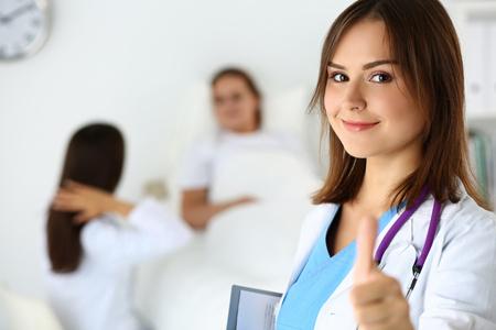 ドキュメント パッドと [ok] を示す親指でサインアップ区フェイント ラウンドを保持している女性医師は笑ってください。高いレベルと品質の医療サ