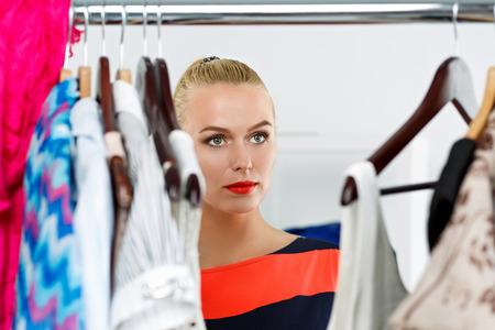 fashion clothing: Beautiful thoughtful blonde woman standing inside wardrobe rack full of clothes suffering with choice. Shopping and consumerism or stylist concept. Nothing to wear and hard to decide concept
