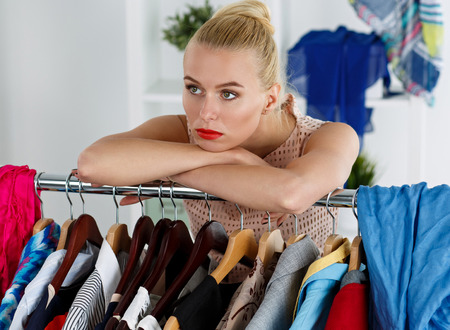 Thoughtful sad beautiful blonde woman standing near wardrobe rack full of clothes and choosing dress. Shopping and consumerism or stylist concept. Nothing to wear and hard to decide concept Banco de Imagens
