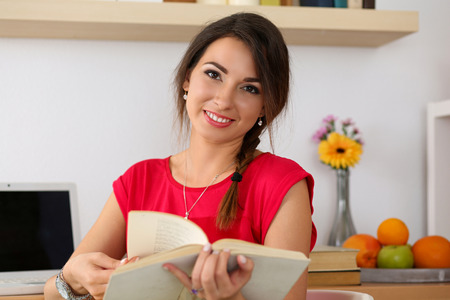self development: Beautiful smiling female student sitting in her room half turn studying. Young brunette woman in red dress at workplace with laptop and opened book preparing for exams. Education and self development Stock Photo
