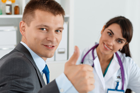 sign up: Smiling man in suit showing OK sign with thumb up at physician reception. High level and quality medical service and care concept. Satisfied happy male patient with medicine doctor at her office