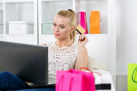 house shopping: Beautiful blonde woman making shopping via internet looking in notebook, paying with credit card. Young lady buying dresses and new stuff in house. Shopping, consumerism, delivery and present concept