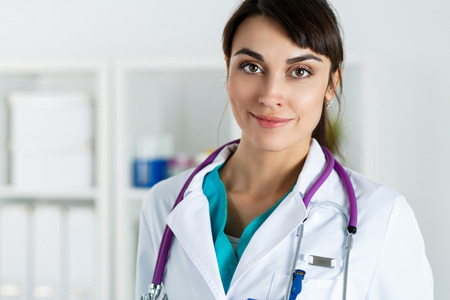 office uniform: Beautiful charming friendly smiling female medicine therapeutist doctor portrait standing in office and looking in camera. Medical help, physician reception and consultation or insurance concept
