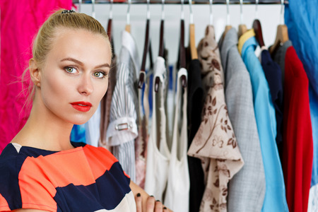 clothes rack: Thoughtful sad beautiful blonde woman standing near wardrobe rack full of clothes and choosing dress. Shopping and consumerism or stylist concept. Nothing to wear and hard to decide concept Stock Photo