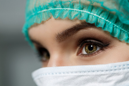 female eyes: Female doctor face wearing protective mask and green surgeon cap closeup. Nurse eyes close up gazing intently. Resuscitation, emergency, save patient life, surgery, medical help and insurance concept