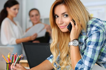 executor: Beautiful blond female designer in office talking cellphone looking in camera doing some notes while her colleagues discussing something in background. Creative people or advertising business concept Stock Photo