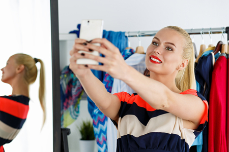 wardrobe closet: Blonde woman standing near wardrobe rack full of clothes and mirror making selfie with cellphone in new dress. Shopping and consumerism or stylist concept. Nothing to wear and hard to decide concept