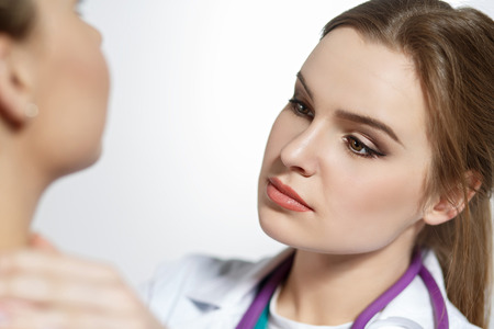 oncologist: Beautiful female medicine doctor with serious face examine patient. Medical care, illness diagnosing, physical, physician consultation, isurance concept. Dermatologist or oncologist examination