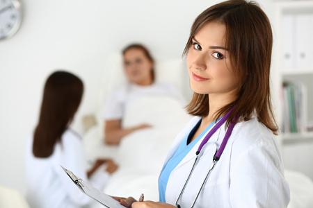 Glimlachende vrouwelijke arts geneeskunde vullen patiënt medische geschiedenis lijst tijdens zaalronde terwijl patiënt communicatie met arts. Gezondheidszorg of verzekering concept. Arts klaar om te onderzoeken en te helpen