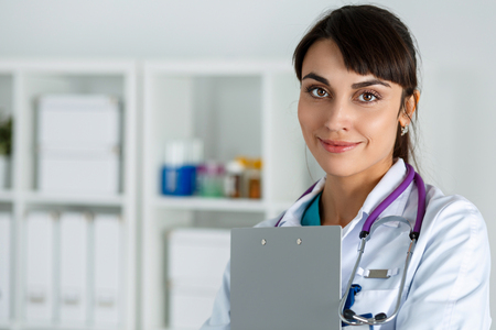 standing reception: Beautiful charming friendly smiling female medicine doctor standing in office, holding document clipboard, looking in camera. Medical help, physician reception and consultation or insurance concept Stock Photo