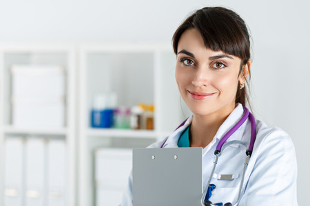 office uniform: Beautiful charming friendly smiling female medicine doctor standing in office, holding document clipboard, looking in camera. Medical help, physician reception and consultation or insurance concept Stock Photo